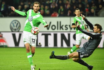 WOLFSBURG, GERMANY - JANUARY 30:  Bas Dost of Wolfsburg chips the ball past Manuel Neuer of Muenchen during the Bundesliga match between VfL Wolfsburg and FC Bayern Muenchen at Volkswagen Arena on January 30, 2015 in Wolfsburg, Germany.  (Photo by Stuart Franklin/Getty Images for MAN)