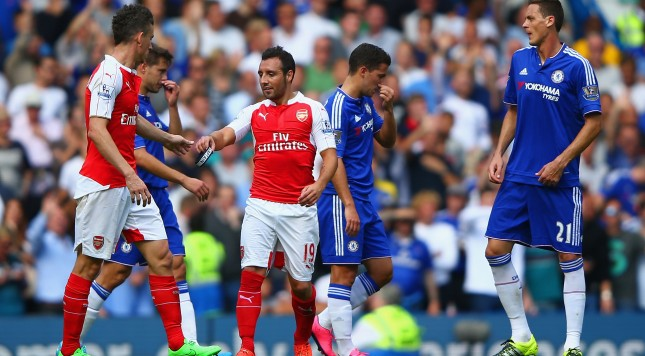 LONDON, ENGLAND - SEPTEMBER 19: Santi Cazorla of Arsenal passes his captain's armband to team mate Laurent Koscielny as he is shown a red card  during the Barclays Premier League match between Chelsea and Arsenal at Stamford Bridge on September 19, 2015 in London, United Kingdom.  (Photo by Ian Walton/Getty Images)