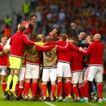 LILLE, FRANCE - JULY 01: Wales players celebrate their team's first goal by Ashley Williams (obscured) during the UEFA EURO 2016 quarter final match between Wales and Belgium at Stade Pierre-Mauroy on July 1, 2016 in Lille, France.  (Photo by Clive Rose/Getty Images)