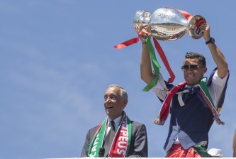 LISBON, PORTUGAL - JULY 11: Portuguese forward Cristiano Ronaldo (R) and Portuguese President Marcelo Rebelo de Sousa (L) showing the European cup to the supporters during the meeting with the Portuguese President Marcelo Rebelo de Sousa for the Portugal Euro 2016 Victory ceremonies at Lisbon on July 11, 2016 in Lisbon, Portugal.  (Photo by Carlos Rodrigues/Getty Images)