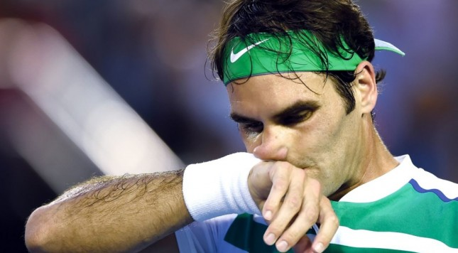 Roger Federer of Switzerland wipes the sweat from his face during his semifinal match against Novak Djokovic of Serbia at the Australian Open tennis championships in Melbourne, Australia, Thursday, Jan. 28, 2016.(AP Photo/Andrew Brownbill)