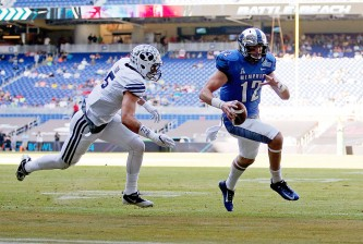 MIAMI, FL - DECEMBER 22:  Paxton Lynch #12 of the Memphis Tigers rushes for a touchdown past defender Alani Fua #5 of the Brigham Young Cougar during the first quarter of the game against the Brigham Young Cougars at Marlins Park on December 22, 2014 in Miami, Florida.  (Photo by Rob Foldy/Getty Images)