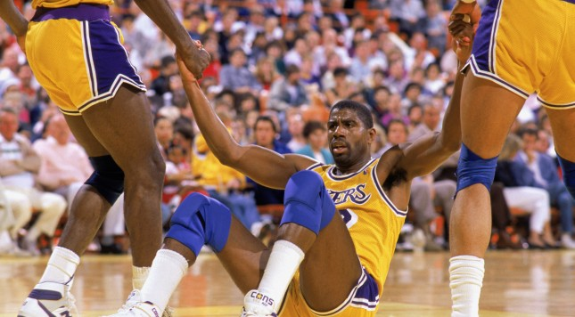 LOS ANGELES - 1987:  Teammates help Magic Johnson #32 of the Los Angeles Lakers off the floor during an NBA game at the Great Western Forum in Los Angeles, California in 1987.  (Photo by: Mike Powell/Getty Images)
