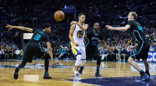 CHARLOTTE, NC - DECEMBER 02: Stephen Curry (30) of the Golden State Warriors makes a no look pass as he is defended by Jeremy Lamb (3), kemba Walker (15) and Cody Zeller (40) of the Charlotte Hornets at Time Warner Cable Arena on December 2, 2015 in Charlotte, North Carolina.  The Warriors defeated the Hornets 116-99.  (Photo by Brian A. Westerholt/Getty Images)