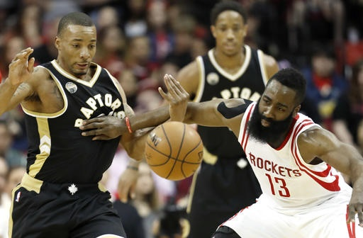 Houston Rockets' James Harden (13) and Toronto Raptors' Norman Powell chase a loose ball during the first quarter of an NBA basketball game Friday, March 25, 2016, in Houston. (AP Photo/David J. Phillip)