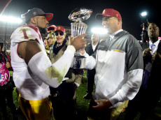 PASADENA, CA - JANUARY 02:  Wide receiver Darreus Rogers #1 of the USC Trojans and head coach Clay Helton celebrate with the 2017 Rose Bowl trophy after defeating the Penn State Nittany Lions 52-49 to win the 2017 Rose Bowl Game presented by Northwestern Mutual at the Rose Bowl on January 2, 2017 in Pasadena, California.  (Photo by Harry How/Getty Images)