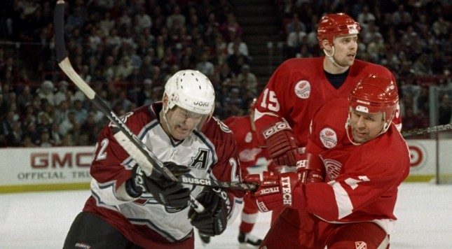 17 Dec 1997:  Rightwinger Claude Lemieux of the Colorado Avalanche (left) in action against defenseman Viacheslav Fetison and leftwinger Tomas Holmstrom of the Detroit Red Wings during a game at the McNichols Sports Arena in Denver, Colorado.  The Red Win