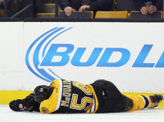BOSTON, MA - JANUARY 05:  Adam McQuaid #54 of the Boston Bruins lays injured on the ice after being checked into the boards head first during the second period against the Washington Capitals at TD Garden on January 5, 2016 in Boston, Massachusetts.  (Photo by Maddie Meyer/Getty Images)