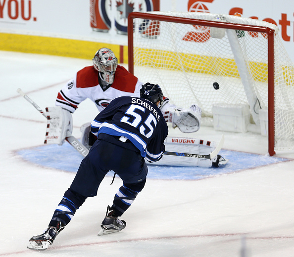 WINNIPEG, MANITOBA - OCTOBER 13: Mark Scheifele #55 of the Winnipeg Jets beats Cam Ward #30 of the Carolina Hurricanes for the overtime game-winning goal during NHL action on October 22, 2016 at the MTS Centre in Winnipeg, Manitoba. (Photo by Jason Halstead /Getty Images)