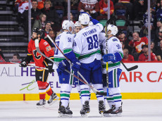 CALGARY, AB - DECEMBER 23: Nikita Tryamkin #88 of the Vancouver Canucks celebrates with his teammates after scoring against the Calgary Flames during an NHL game at Scotiabank Saddledome on December 23, 2016 in Calgary, Alberta, Canada. (Photo by Derek Leung/Getty Images)