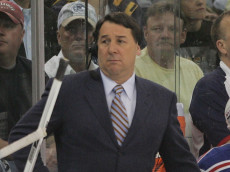 PITTSBURGH - MAY 04: TV commentator Mike Milbury works between the benches in the game between the Pittsburgh Penguins and the New York Rangers during game five of the Eastern Conference Semifinals of the 2008 NHL Stanley Cup Playoffs on May 4, 2008 at the Mellon Arena in Pittsburgh, Pennsylvania. The Penguins defeated the Rangers 3-2 in overtime to win the series 4 games to 1.  (Photo by Bruce Bennett/Getty Images)