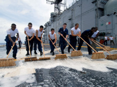 070706-N-5588M-003 ATLANTIC OCEAN (July 6, 2007) - Aboard amphibious assault ship USS Nassau (LHA 4), Sailors from the crash and salvage team sweep down the flight deck during an aqueous film forming foam (AFFF) countermeasure wash down. Nassau is on a scheduled underway period to test various aspects of the ships combat readiness. U.S. Navy photo by Mass Communication Specialist Seaman Michael Minkler (RELEASED)