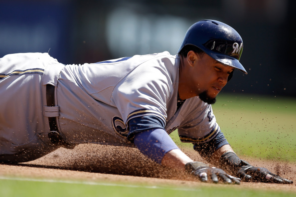 SAN FRANCISCO, CA - AUGUST 31: Carlos Gomez #27 of the Milwaukee Brewers slides in to third base on a triple hit by Jonathan Lucroy #20 in the first inning of their game against the San Francisco Giants at AT&T Park on August 31, 2014 in San Francisco, California.  (Photo by Ezra Shaw/Getty Images)