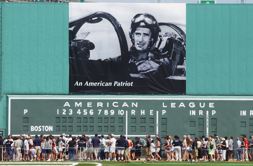 BOSTON - JULY 22:  Fans walk past a poster of Ted Williams during his military service in Korea sitting in his fighter jet hanging over the Green Monster before the Ted Williams tribute on July 22, 2002 at Fenway Park in Boston, Massachusetts. The public was invited to the park to honor Williams who died July 5, 2002.  (Photo by Darren McCollester/Getty Images)
