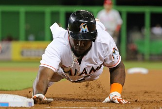 MIAMI, FL - SEPTEMBER 23: Marcell Ozuna #13 of the Miami Marlins dives back to first during a game against the Philadelphia Phillies at Marlins Park on September 23, 2015 in Miami, Florida.  (Photo by Mike Ehrmann/Getty Images)