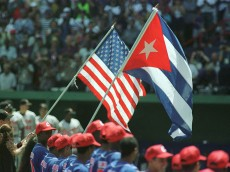 28 Mar 1999: The Baltimore Orioles and the Cuba National Team pause under the flags for the national anthems before taking the field at Estadio Latinoamericano in Havanna, Cuba. Mandatory Credit: Matthew Stockman/ALLSPORT