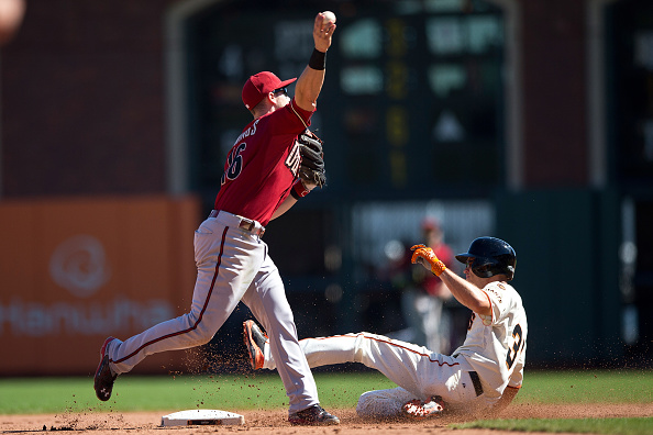 SAN FRANCISCO, CA - SEPTEMBER 20:  Chris Owings #16 of the Arizona Diamondbacks throws after forcing out Kelby Tomlinson #37 of the San Francisco Giants at second base but didn't get the double play at first base in the fifth inning at AT&T Park on September 20, 2015 in San Francisco, California. The San Francisco Giants defeated the Arizona Diamondbacks 5-1.  (Photo by Jason O. Watson/Getty Images)