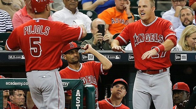 HOUSTON, TX - SEPTEMBER 22: Albert Pujols #5 of the Los Angeles Angels of Anaheim receives congratulations from Mike Trout #27 after hitting a home run in the first inning against the Houston Astros at Minute Maid Park on September 22, 2015 in Houston, Texas. (Photo by Bob Levey/Getty Images)