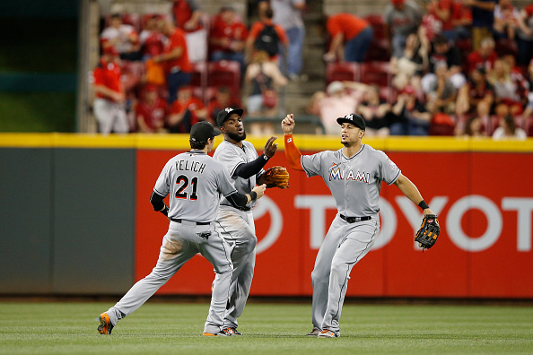 CINCINNATI, OH - JUNE 20: Christian Yelich #21, Marcell Ozuna #13 and Giancarlo Stanton #27 of the Miami Marlins celebrate after the final out of the game against the Cincinnati Reds at Great American Ball Park on June 20, 2015 in Cincinnati, Ohio. The Marlins defeated the Reds 5-0. (Photo by Joe Robbins/Getty Images)