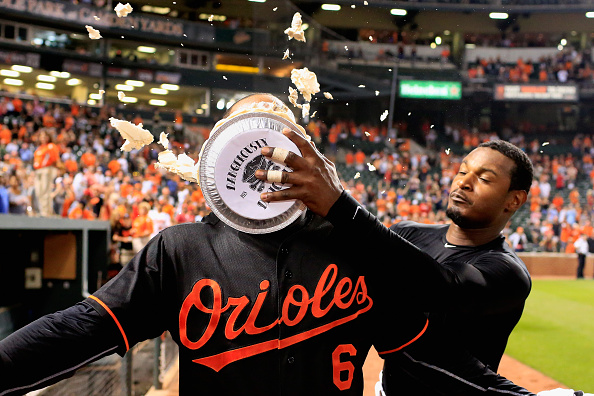 BALTIMORE, MD - JULY 10: Adam Jones #10 hits Jonathan Schoop #6 of the Baltimore Orioles with a pie after Schoop hit a walk off home run giving the Orioles a 3-2 win over the Washington Nationals at Oriole Park at Camden Yards on July 10, 2015 in Baltimore, Maryland.  (Photo by Rob Carr/Getty Images)