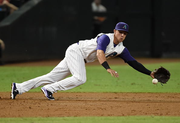 PHOENIX, AZ - OCTOBER 01:  Jake Lamb #19 of the Arizona Diamondbacks makes a diving play on a ground ball during the first inning against the Colorado Rockies at Chase Field on October 1, 2015 in Phoenix, Arizona.  (Photo by Norm Hall/Getty Images)