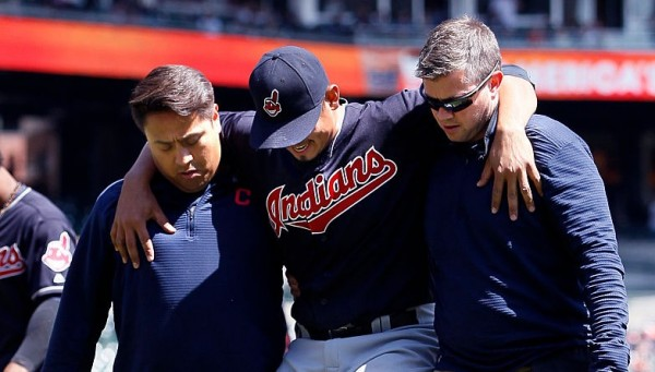 DETROIT, MI - APRIL 24:  Carlos Carrasco #59 of the Cleveland Indians is helped off the field by trainers Michael Salazar, left, and James Quinlan, right, after injuring his left leg making an out on Andrew Romine of the Detroit Tigers at first base during the third inning at Comerica Park on April 24, 2016 in Detroit, Michigan. (Photo by Duane Burleson/Getty Images)