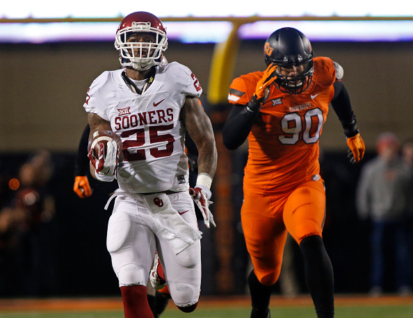 STILLWATER, OK - NOVEMBER 28 : Running back Joe Mixon #25 of the Oklahoma Sooners outruns defensive end Trace Clark #90 of the Oklahoma State Cowboys for a touchdown November 28, 2015 at Boone Pickens Stadium in Stillwater, Oklahoma. (Photo by Brett Deering/Getty Images)