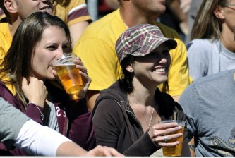 Minnesota fans drink beer during an NCAA college football game against New Hampshire, Saturday, Sept. 8, 2012, in Minneapolis. The game was the first where fans could purchase beer at TCF Stadium. Minnesota won 44-7. (AP Photo/Tom Olmscheid)