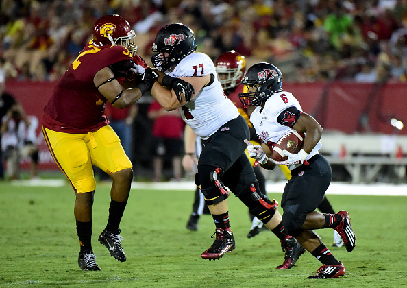 LOS ANGELES, CA - SEPTEMBER 05:  Warren Wand #6 of the Arkansas State Red Wolves carries the ball as he gets a block from Daniel Keith #77 on Delvon Simmons #52 of the USC Trojans during the second quarter at Los Angeles Coliseum on September 5, 2015 in Los Angeles, California.  (Photo by Harry How/Getty Images)