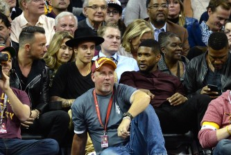 CLEVELAND, OH - OCTOBER 30: Singers Justin Bieber (2nd L) and Usher look on during a game between the Cleveland Cavaliers and the New York Knicks at Quicken Loans Arena on October 30, 2014 in Cleveland, Ohio. NOTE TO USER: User expressly acknowledges and agrees that, by downloading and or using this photograph, User is consenting to the terms and conditions of the Getty Images License Agreement.  (Photo by Jason Miller/Getty Images)
