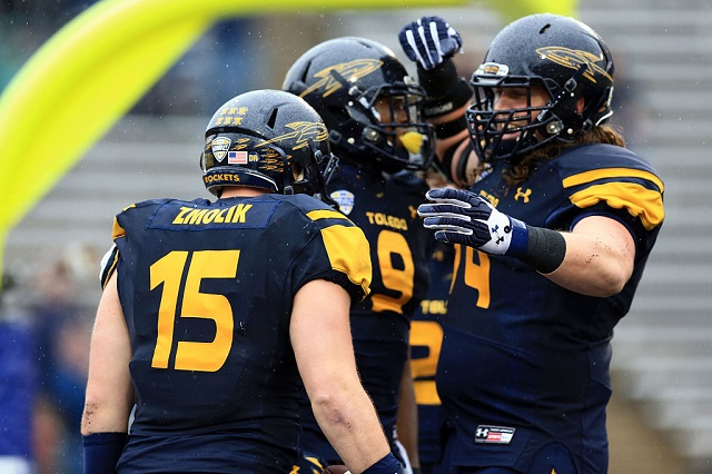 TOLEDO, OH - NOVEMBER 27: Tight end Alex Zmolik #15 of the Toledo Rockets celebrates with teammates after catching a pass for a touchdown during the first quarter against the Western Michigan Broncos at Glass Bowl on November 27, 2015 in Toledo, Ohio. Western Michigan Broncos defeated Toledo Rockets 35-30. (Photo by Andrew Weber/Getty Images)
