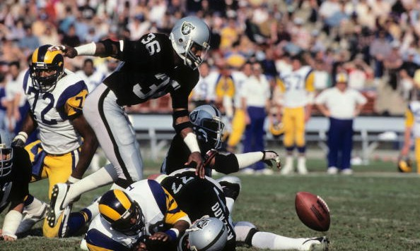 LOS ANGELES, CA - DECEMBER 18:  Mike Davis #36 of the Los Angeles Raiders chases after a fumble caused by teammate Lyle Alzedo #77 on running back Wedell Tyler #26 of the Los Angeles Rams during the game at the Los Angeles Memorial Coliseum on December 18, 1982 in Los Angeles, California.  The Raiders won 37-31. (Photo by George Rose/Getty Images)
