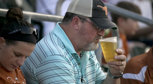 A spectator sips a tall cold beer now on sale at teh stadium. The University of Texas baseball team played host to Texas State in a non-conference game at UFCU Disch-Falk Field Tuesday evening April 21, 2015.  RALPH BARRERA/ AMERICAN-STATESMAN