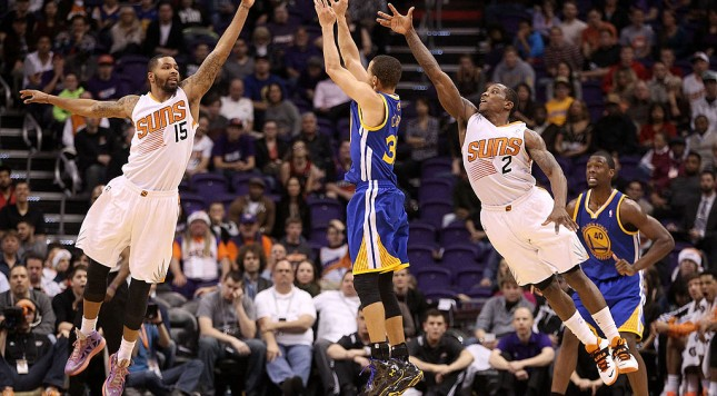 PHOENIX, AZ - DECEMBER 15:  Stephen Curry #30 of the Golden State Warriors puts up a three point shot against Marcus Morris #15 and Eric Bledsoe #2 of the Phoenix Suns during the second half of the NBA game at US Airways Center on December 15, 2013 in Phoenix, Arizona. The Suns defeated the Warriors 106-102. NOTE TO USER: User expressly acknowledges and agrees that, by downloading and or using this photograph, User is consenting to the terms and conditions of the Getty Images License Agreement.  (Photo by Christian Petersen/Getty Images)