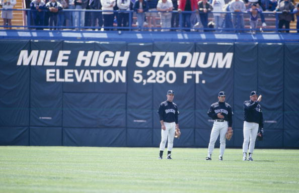 DENVER - APRIL 15:  Colorado Rockies players stand in the outfield with at Mile High Stadium elevation sign in background before the game against the New York Mets on April 15, 1993 in Denver, Colorado. (Photo by Tim DeFrisco/Getty Images)