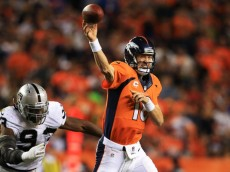 DENVER, CO - SEPTEMBER 23:   Peyton Manning #18 of the Denver Broncos passes under pressure from  Jason Hunter #93 of the Oakland Raiders at Sports Authority Field at Mile High on September 23, 2013 in Denver, Colorado.  (Photo by Doug Pensinger/Getty Images)