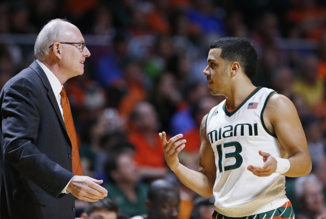 Miami head coach Jim Larranaga, left, talks with guard Angel Rodriguez (13) during the first half of an NCAA college basketball game against Louisville, Saturday, Feb. 27, 2016, in Coral Gables, Fla. Miami defeated Louisville 73-65. (AP Photo/Wilfredo Lee)