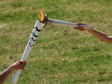 OLYMPIA, GREECE -  APRIL 20:  Actress Katerina Lechou (R) acting the high pristess passes the flame from the Olympic Torch at the Ancient Stadium during the Rehearsal for the Lighting Ceremony of the Olympic Flame at Ancient Olympia on April 20, 2016 in Olympia, Greece.  (Photo by Milos Bicanski/Getty Images)