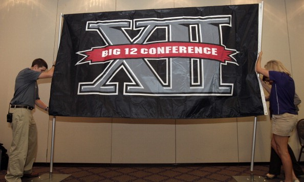 FORT WORTH, TX - OCTOBER 10:  Texas Christian University sophomore Zach Boring (L), and freshman Laura Dunn raise a Big XII Conference banner before a press conference in which TCU accepted an invention to join the Big XII on October 10, 2011 in Fort Worth, Texas. (Photo by Brandon Wade/Getty Images)