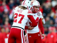 PISCATAWAY, NJ - NOVEMBER 14:  Drew Brown #34 of the Nebraska Cornhuskers is congratulated by teammate Sam Foltz #27 after Brown kicked the extra point in the first half against the Rutgers Scarlet Knights on November 14, 2015 at High Point Solutions Stadium in Piscataway, New Jersey.  (Photo by Elsa/Getty Images)