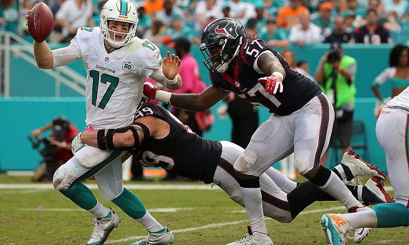 MIAMI GARDENS, FL - OCTOBER 25:  Ryan Tannehill #17 of the Miami Dolphins is sacked by J.J. Watt #99 of the Houston Texans during a game  at Sun Life Stadium on October 25, 2015 in Miami Gardens, Florida.  (Photo by Mike Ehrmann/Getty Images)