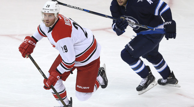 WINNIPEG, MANITOBA - OCTOBER 13: Paul Postma #4 of the Winnipeg Jets and Bryan Bickell #29 of the Carolina Hurricanes head to the Carolina zone during NHL action on October 22, 2016 at the MTS Centre in Winnipeg, Manitoba. (Photo by Jason Halstead /Getty Images)