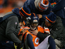 DENVER, CO - DECEMBER 28:  Strong safety David Bruton #30 of the Denver Broncos is attended to by trainers after a play that would force him out of the game with a reported concussion during a game against the Oakland Raiders at Sports Authority Field at Mile High on December 28, 2014 in Denver, Colorado.  (Photo by Doug Pensinger/Getty Images)