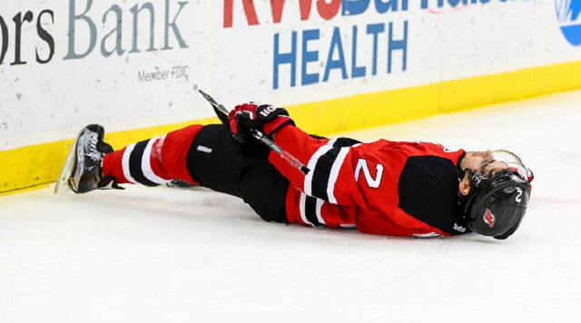 NEWARK, NJ - DECEMBER 31:  New Jersey Devils defenseman John Moore (2) lies motionless on the ice after getting hit into the boards by Washington Capitals right wing Tom Wilson (43)(not pictured) during the first period of the National Hockey League game between the New Jersey Devils and the Washington Capitals  on December 31, 2016, at the Prudential Center in Newark, NJ.   (Photo by Rich Graessle/Icon Sportswire via Getty Images)