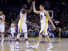 :OAKLAND, CA - JANUARY 23: Klay Thompson #11 of the Golden State Warriors is congratulated by Draymond Green #23 after he made a basket in the third quarter of their game against the Sacramento Kings at ORACLE Arena on January 23, 2015 in Oakland, California. Thompson scored 37 points in the third quarter to set a NBA record.  (Photo by Ezra Shaw/Getty Images)