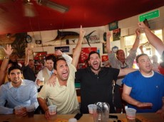 MIAMI - JUNE 23:  Frank Mena (2L), Ricardo Martinez (2R), Mark Kerr (R) and others celebrate the winning goal for the USA soccer team while watching the 2010 FIFA World Cup South Africa Group C match between USA and Algeria on television at Churchill's pub on June 23, 2010 in Miami, Florida.  The United States team will advance to the second round at the World Cup with a 1-0 win over Algeria.  (Photo by Joe Raedle/Getty Images)