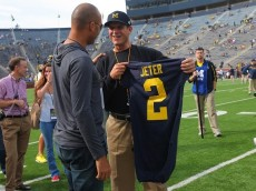 ANN ARBOR, MI - SEPTEMBER 26: Head coach Jim Harbaugh (R) of the Michigan Wolverines presents baseball great Derek Jeter (L) of the New York Yankees with a jersey prior to the game against the Brigham Young Cougars at Michigan Stadium on September 26, 2015 in Ann Arbor, Michigan. (Photo by Doug Pensinger/Getty Images)