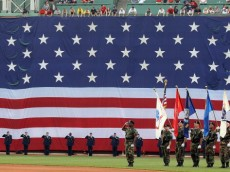 BOSTON, MA - MAY 30:  To honor Memorial Day, a giant flag covers the Green Monster as the national anthem is played on May 30, 2011 at Fenway Park in Boston, Massachusetts.  (Photo by Elsa/Getty Images)