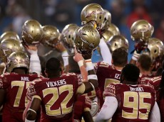 CHARLOTTE, NC - DECEMBER 06: Johnathan Vickers #22 and Keith Bryant #95 of the Florida State Seminoles join a team huddle before the game against the Georgia Tech Yellow Jackets at the ACC Championship game on December 6, 2014 in Charlotte, North Carolina. (Photo by Mike Ehrmann/Getty Images)