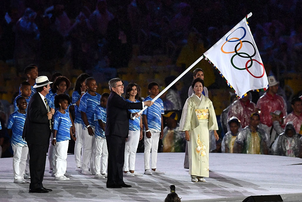 RIO DE JANEIRO, BRAZIL - AUGUST 21:  (L-R) Mayor of Rio de Janeiro Eduardo Paes, IOC President Thomas Bach and Governor of Tokyo Yuriko Koike take part in the Flag Handover Ceremony during the Closing Ceremony on Day 16 of the Rio 2016 Olympic Games at Maracana Stadium on August 21, 2016 in Rio de Janeiro, Brazil.  (Photo by David Ramos/Getty Images)